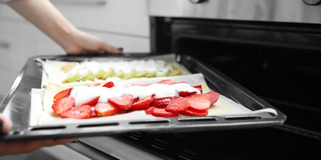 Female hands placing strawberry and apple desserts into oven